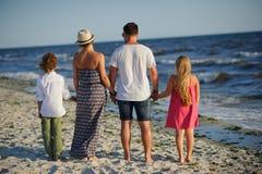 Объединенная семья из четырех человек восхищает море Стоковые Фотографии RF