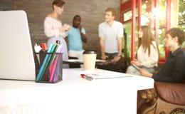 Объединяйтесь в команду молодые профессионалы имея вскользь обсуждение в офисе Исполнительные власти имея дружелюбное обсуждение  Стоковое Изображение RF