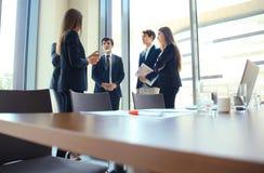 Объединяйтесь в команду молодые профессионалы имея вскользь обсуждение в офисе Исполнительные власти имея дружелюбное обсуждение  Стоковое Изображение