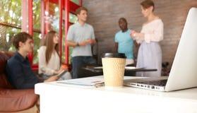 Объединяйтесь в команду молодые профессионалы имея вскользь обсуждение в офисе Исполнительные власти имея дружелюбное обсуждение  Стоковое Фото