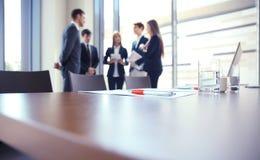 Объединяйтесь в команду молодые профессионалы имея вскользь обсуждение в офисе Исполнительные власти имея дружелюбное обсуждение  Стоковые Фото