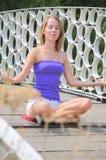 объезжает девушку ее практикуя йога релаксации Стоковые Изображения