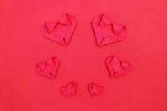 объезжайте 6 складывая красных бумажных сердец на красном цвете для картины валентинки Стоковая Фотография