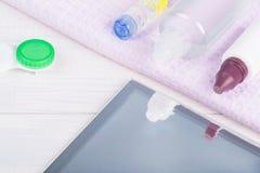 Объектив для коррекции зрения и комплект продуктов и хранения заботы положены вне на светлую предпосылку Стоковая Фотография RF
