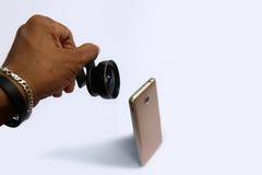 Объектив зажима с мобильными телефонами в белой предпосылке Стоковое Фото