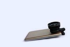 Объектив зажима с мобильными телефонами в белой предпосылке Стоковые Фотографии RF