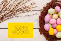 Объекты пасхи традиционные на деревянных egss предпосылки в вербе гнезда и поздравительной открытке стоковое фото