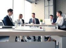 Объединяйтесь в команду молодые профессионалы имея вскользь обсуждение в офисе Исполнительные власти имея дружелюбное обсуждение  Стоковое фото RF