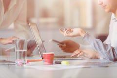 Объединяйтесь в команду обсуждающ проект на компьютере на современном офисе Стоковое Изображение RF