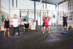 Объединяйтесь в команду разминка с весами в центре спортзала фитнеса Стоковое фото RF