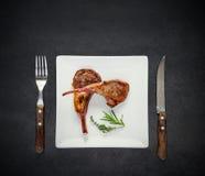 Объягнитесь стейк на белых вилке и ноже острословия плиты Стоковые Изображения RF