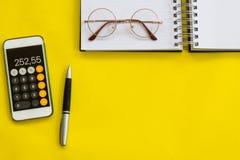 Объяснение, финансовая концепция, плоское положение или взгляд сверху ручки, умного телефона с калькулятором с белым блокнотом на стоковое фото