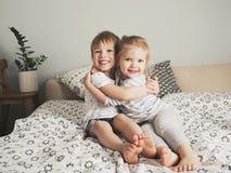 Объятие 2 милое усмехаясь детей на кровати Стоковое Фото