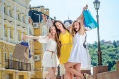 Объятие подруги счастливое 3 друз держа хозяйственные сумки и Ра Стоковые Фотографии RF