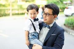 Объятие сына его отец и улыбка со случайным костюмом в парке стоковое фото rf