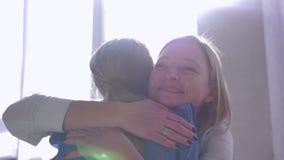 Объятия матери, спешка маленькой девочки в руки мамы и дают большую обнимают и целуют дома против окна в лучах солнца