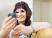 Обычная женщина используя электронное устройство Стоковое Изображение