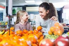 Обычная мать и дочь покупая зрелые плодоовощи Стоковые Изображения