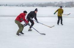 Обычные люди игры hokey на замороженном реке Dnipro в Украине стоковое фото