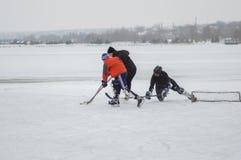 3 обычные люди игры hokey на замороженном реке Dnipro в Украине стоковое фото rf