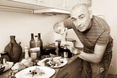 Обычный человек брызгает с салатом перца на плите Стоковое Изображение RF