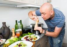 Обычный человек брызгает с салатом перца на плите Стоковые Фото