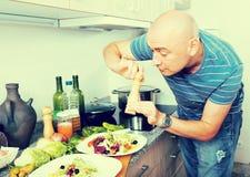 Обычный человек брызгает с салатом перца на плите Стоковая Фотография RF
