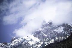 Облака лежат на покрытых снег верхних частях утесов Ландшафт тонна Стоковое фото RF