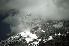 Облака лежат на покрытых снег верхних частях утесов Ландшафт тонна Стоковое Изображение RF