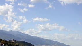 Облака летают над горами и средневековой крепостью видеоматериал