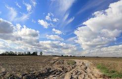 Облака над грязной улицей в поле стоковые фотографии rf