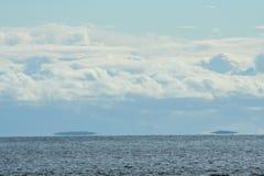 Облака над морем, островом на горизонте, живой природой северной Стоковые Изображения