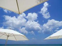 Облака обрамленные зонтиками пляжа стоковая фотография rf