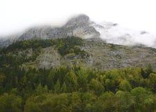 Облака свертывают в и над горных вершинах Стоковые Изображения