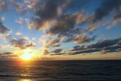 Облака участвуют в гонке к заходящему солнцу Стоковые Изображения RF