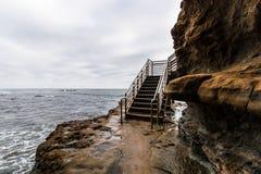 Облака шторма над лестницами доступа океана скал захода солнца стоковое фото rf