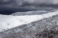 Облако маяча над снегом покрыло горы Стоковое фото RF