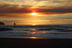 Облачные небеса и заход солнца над Орегоном плавают вдоль побережья выходы на поверхность Тихого океана скалистые Стоковое Изображение RF