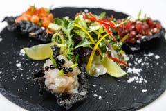 Обломоки закуски железистые заполненные с морепродуктами на каменной доске на белизне стоковые изображения