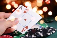Обломоки казино и пары тузов в croupier& x27; рука s против ярких светов bokeh Концепция темы игры в покер Стоковые Фото