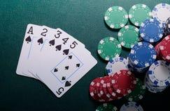 Обломоки казино и прямая комбинация карточек на зеленой таблице Концепция игры в покер Стоковая Фотография RF