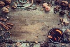 Обдумыванное вино в черной деревенской кружке с специями и ингридиентами Стоковые Фото