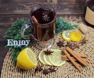 Обдумыванное вино с циннамоном, anisetree, можжевельник и надпись наслаждаются Стоковая Фотография