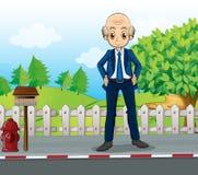 Облыселый значок дела стоя на дороге около деревянного mailbo Стоковые Фото