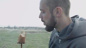 Облыселый, красивый человек в природе ест зажаренный в духовке хлеб зажаренный на ручке над огнем акции видеоматериалы