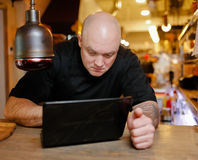 Облыселый молодой человек смотря компьтер-книжку Стоковая Фотография