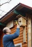 Облыселый старший с усиком прикрепляет birdhouse к амбару стоковое фото