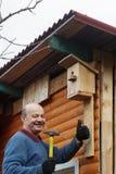 Облыселый старший с усиком прикрепляет birdhouse к амбару стоковые изображения