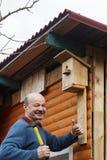 Облыселый старший с усиком прикрепляет birdhouse к амбару стоковая фотография