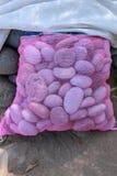 Овальные камни в пурпурном мешке на черном вулканическом песке Море работало валуны Естественный строительный материал Камни лавы стоковая фотография